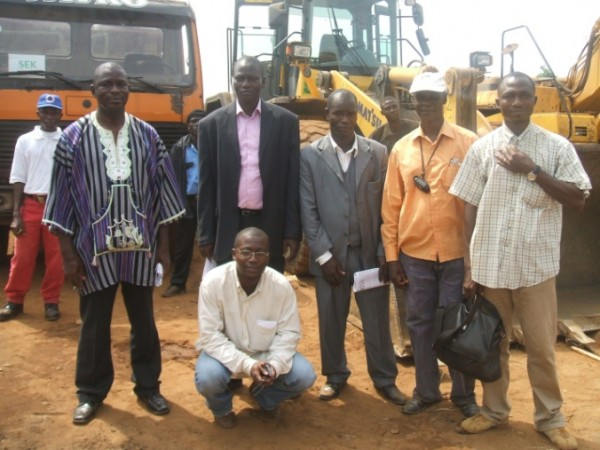 Officials of SEK Liberia, with some equipment at the back