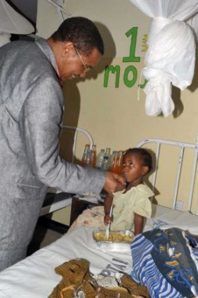 President consoles a child in Amana Hospital