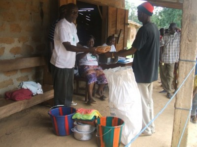 A Staff of LDS presents items to one of the beneficiaries