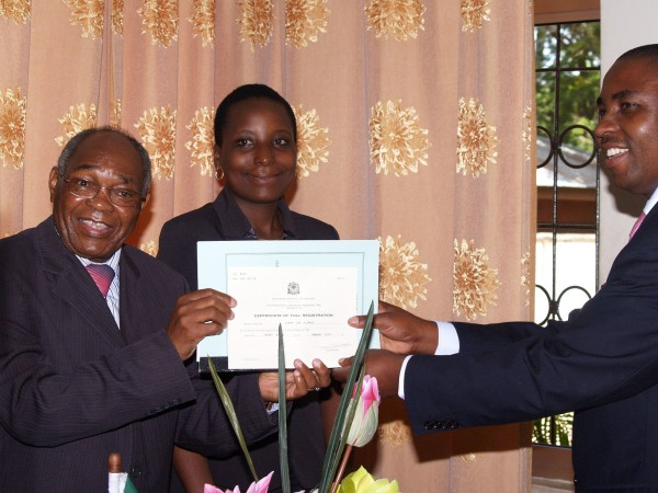 A jubilant CCK's chairman Constantine Akitanda (R), holding a party registration certificate with John Tendwa (L) the registrar of political parties.