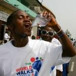 Women walk for water, while a youth drinks from a locally produced water bag