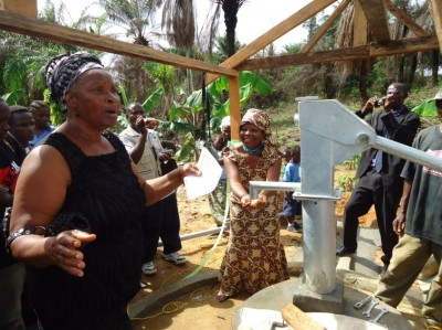 An Elderly woman of Arthington Township sings and dances for the new source of safe water provided, while Higher Ground International CEO, Madam Henrietta White-Holder fetches water to drink
