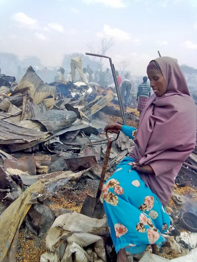 A woman tries to salvage for unburnt goods in her shop after a severe fire broke out in the main market of Dagahaley refugee camp © Moulid Hujale/IRIN