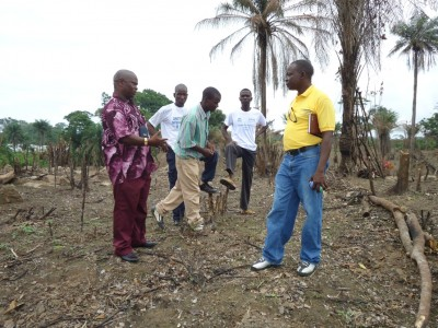 LDS Assistant Program Officer, Vandi Kallon (left) speaking to a staff and some of the refugees, during their visit to a newly cleared 120 acres of farm land by Ivorian refugees in the Bahn Refugee Camp, Nimba County