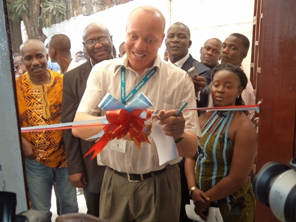 WaterAid Team Leader, Apollos Nwafor cuts the ribbons on behalf of the Coordinator (now former) of the Liberia WASH Consortium, Samuel Pieh(standing directly at the back with a pair of glasses), at the official opening ceremonies of the Headquarters of the WASH Reporters & editors Network of Liberia, held Monday, March 18, 2012 on Carey Street-Crown Hill in Central Monrovia