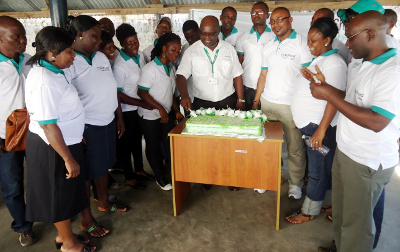 Cutting of the Anniversary Cake by ChildFund-Liberia's Acting Country Director,             Godfrey Mwelwa, amidst smiles on the faces of staff of ChildFund-Liberia