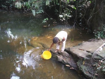 A little girl fetches creek water