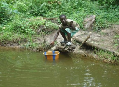 A kid demonstrating how residents of Gwekpozue Town used to fetch water here, prior to the construction of the of the above hand pump by Living Water Int'l-Liberia