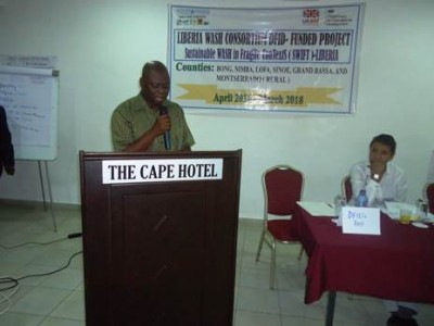 "Board of the Liberia WASH Consortium ""Oxfam"" Country Director, Mamudu Salifu making opening remarks at the Launch of the Project"