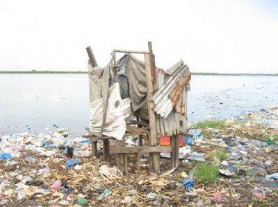 A goal post toilet on the banks of the Du River in Slipway, surrounded by trash