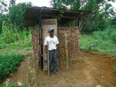 (AFTER) Blind Oldman, John Gweh of Kwenkor in Cape Mount, standing in front of a toilet built by himself