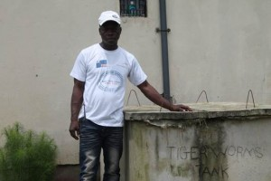 A beneficiary, Morris Gbagee standing beside the Tiger worms Toilet
