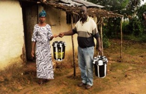 Arthington City Mayor presenting a hand washing bucket with anti-Ebola items to a woman in front of her house in one of the towns
