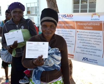 Women hold up their beneficiary ration cards at a distribution site in Bulilima District, Matabeleland South Province. USAID provides rations of fortified corn soy blend and vegetable oil to pregnant and lactating women and children under two years of age.