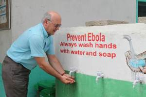 Oxfam Chief Executive, Mark Goldring demonstrating hand washing during a visit to Logan Town