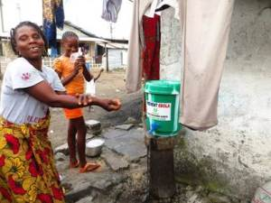 A Community resident washing her Hands as part of preventive measures