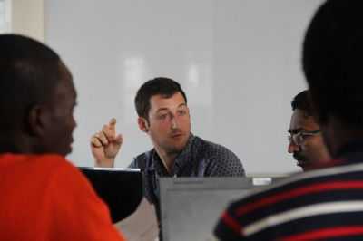 Global Communities Sector 4 Co-Coordinator Josh Balser meets with the Ebola response team to map out the spread of a recent cluster outbreak and plan containment response.