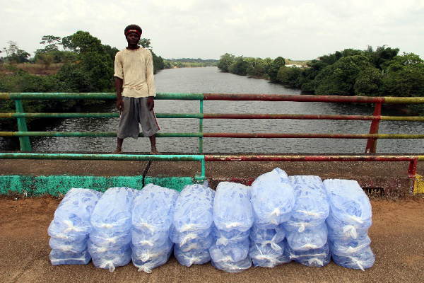 Economic activity has suffered with closed borders. A Liberian man waits with a shipment of water sacks on the Mono River Bridge. With the Sierra Leone border still closed on Wednesday, he could not take his truck across. He waits for a Sierra Leonean contact to pick up the shipment and complete the delivery.
