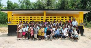 Some students and staff of the Dinnatah Public School in Gibi District, Margibi County along with others joyfully standing in front of the modern latrine constructed by Living Water International