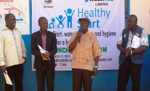 """Healthy Start officially launched by Health Authorities """"D. Omarley Yeabah with microphone, Dr. Fred Amegashie(R), and Amos Gborie(L)"""", while WaterAid's Team Leader, Chuchu K. Selma looks on with smiles"""