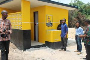 Modern latrine of the Hope Christian Mission School in Weala, Margibi County about to be dedicated, as the Country Director of Living Water International Liberia, Austin Nyaplue and others prepare