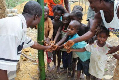 Children from Cotton Tree, an ebola-affected village using a new reed-based hand washing station