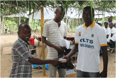 A Natural Leader(R) receiving pocket size radio from LWI Country Director, Austin Nyaplue(L)
