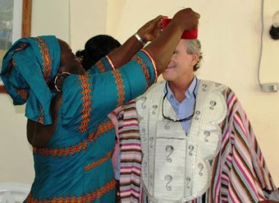Outgoing Global Communities Chief of Party, Piette deVries gowned by Traditional Leader