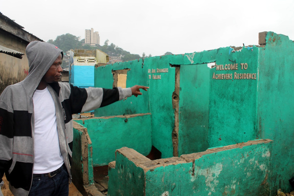 Haji Massaquoi pointing to a house with a tiger worms toilet destroyed by the sea