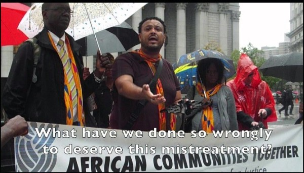 Amaha Kassa 2nd left, founder and Executive Director of African Communities Together leads a rally to Save TPS under drenching rain outside US Immigration building at Federal Plaza in downtown New York City