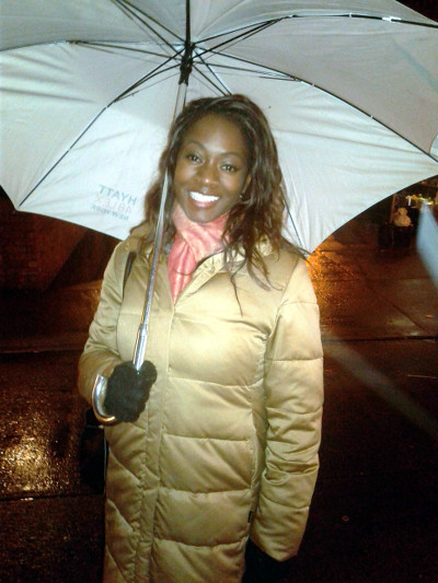 Azania shelters from the rain after an interview at Lido Restaurant in Harlem, New York