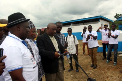 Cutting of ribbon to mark the official dedication of the modern latrine facilities