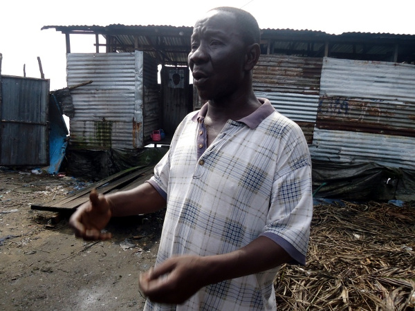 One of the caretakers explains some of the challenges faced  at public toilets in Monrovia (a public toilet in the back)