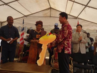 Chinese Ambassador to Liberia, Zhao Jianhua presents a symbolic key to President Ellen Johnson-Sirleaf to the 50 borehole wells, as Public Works Minister (left) and others look with smiles