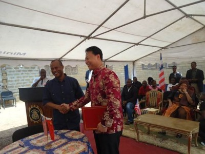 Exchange of a handshake between Chinese Ambassador to Liberia, Zhao Jianhua and Public