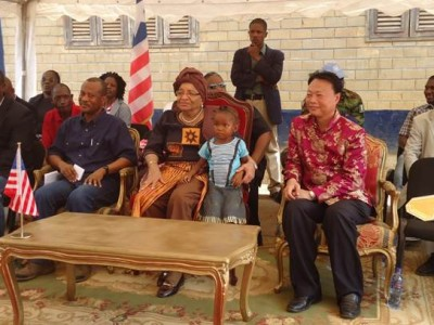 "President Ellen Johnson-Sirleaf and a little girl from the Mount Barclay Community seated in the same Executive Chair ""Sign of Motherhood"" during the program"
