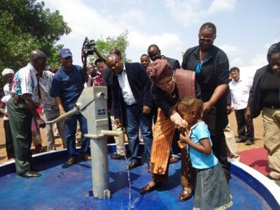 President Ellen Johnson-Sirleaf feeds a little girl with water, after officially dedicating the Mount Barclay Hand Pump, one of the 50 borehole wells sponsored by the Chinese Embassy in Monrovia